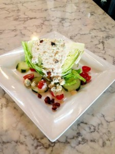 Blue Water Wedge – Crisp Iceberg with cucumbers, grape tomatoes, house-smoked bacon, crumbled Hook's blue cheese and our jalapeño buttermilk dressing